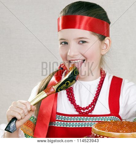 girl  licks a spoon with red caviar