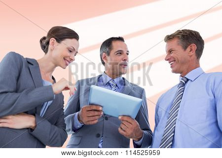 Businessman showing tablet to his colleagues against red vignette