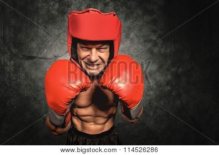 Angry boxer with gloves and headgear against dark background