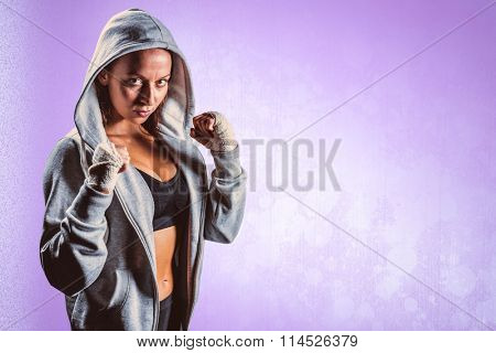 Portrait of female boxer in hood with fighting stance against purple background