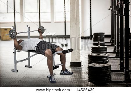 Fit man exercising with barbell against barbell disc plates arranged