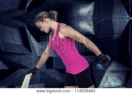 Muscular woman exercising with dumbbells against dark room