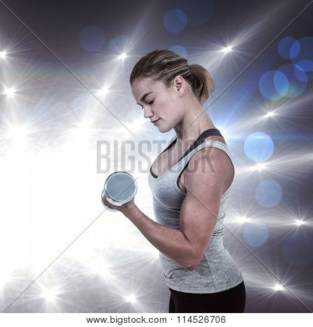 Muscular woman working out with dumbbells against spotlights Muscular woman working out with dumbbells on white background