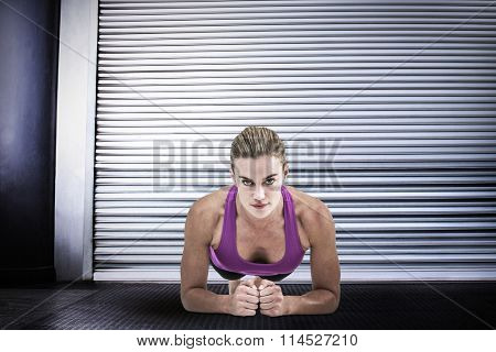 Muscular woman doing push ups against shutter in gym