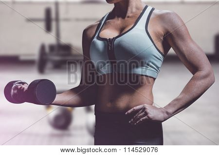 Midsection of woman lifting dumbbell against weights on the studio floor