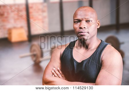 Portrait of bald bodybuilder with arms crossed against gym
