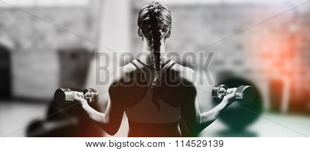 Rear view of braided hair woman lifting dumbbells against weights on the studio floor