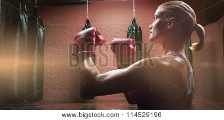 Side view of female boxer with fighting stance against punching bags in red boxing area