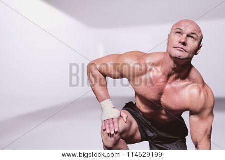 Bodybuilder exercising against black background against abstract room