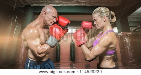 Side view of boxers with fighting stance against red boxing area with punching bags