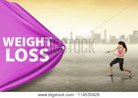 Woman Pulls Weight Loss Text Outdoors