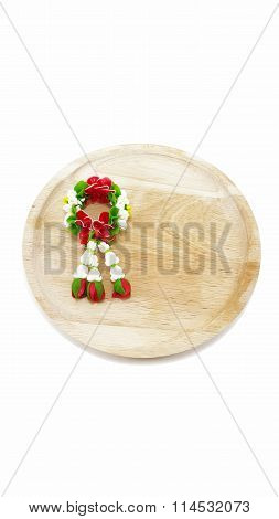 Miniature jasmine garland on wooden plate with white background