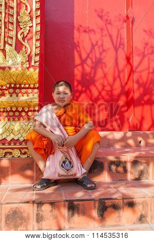 Lumphun Thailand - Jan 8 : Thai Little Monk Sitting In Front Of Buddha Church Door In Pra That Harip