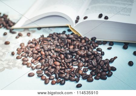 roasted coffee beans on the background of an open book