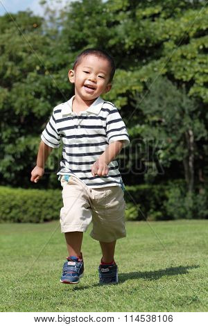 Japanese boy running on the grass (3 years old)