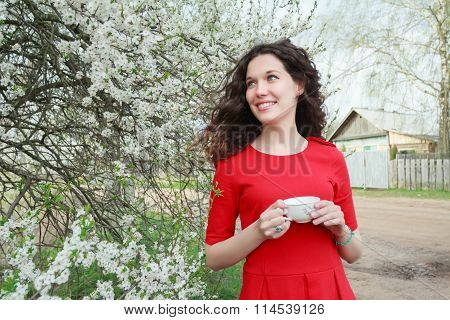 Attractive girl with long dark hair holding teacup and laughing at background of white fruit tree in