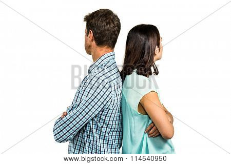 Couple ignoring each other while standing back to back against white background