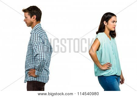 Frustrated couple ignoring each other while standing against white background