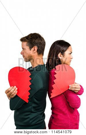 Serious couple standing back to back against white background