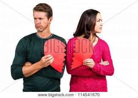 Serious couple holding cracked heart shape on white background