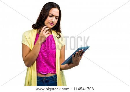Confused woman using digital tablet while standing on white background