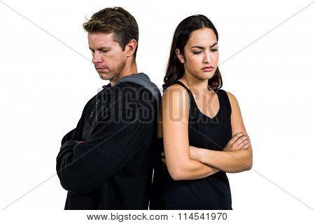 Angry couple standing back to back over white background