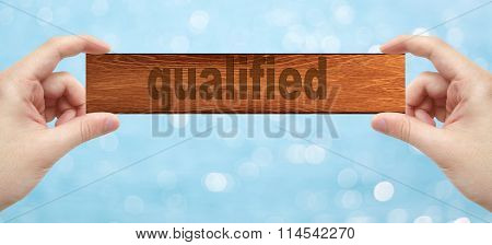 Hands Holding A Wood Engrave With Word Qualified