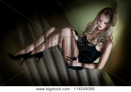 Attractive sexy young woman wrapped in black lingerie sitting on the floor in semidarkness. Sensual