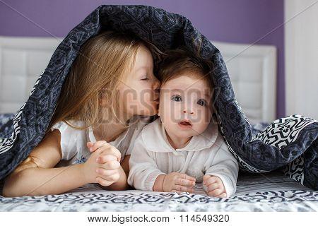 Two sisters lying on the bed under the blanket