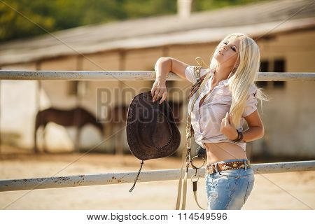 Portrait of beautiful woman - cowgirl, on the ranch in the summer
