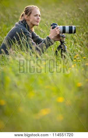 Pretty young woman with a DSLR camera outdoors, using a tripod, taking pictures