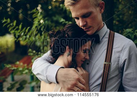 groom gently embracing his bride
