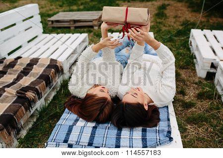 Girls lie and unpacks a gift
