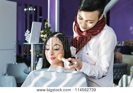 Beautiful young girl in a beauty salon. Doing make-up.