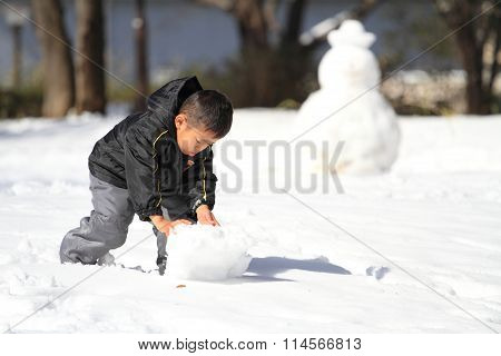Japanese boy making snowman (4 years old)