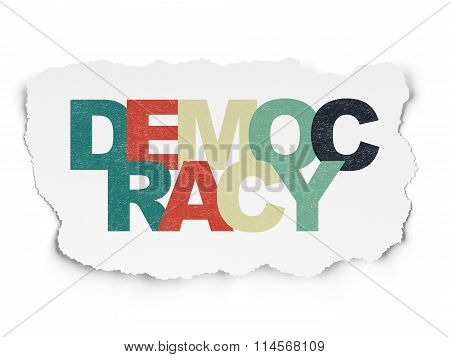 Politics concept: Democracy on Torn Paper background