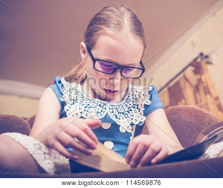 Girl reading a book at home sitting in an armchair.