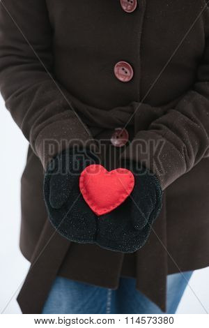 Red decorative heart in hands of women. Gift Valentines Day