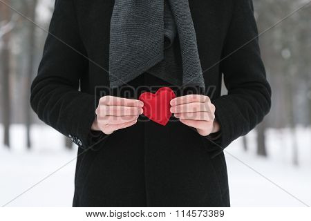 Valentines Day. Man holding a red decorative heart