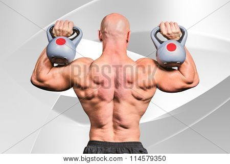 Rear view of bald man lifting kettlebells against white angular design