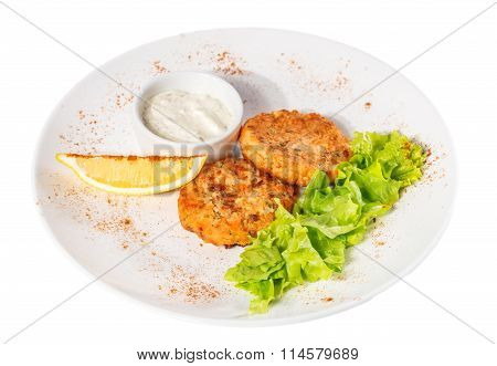 Cutlets with salad leaves, sauce and lemon