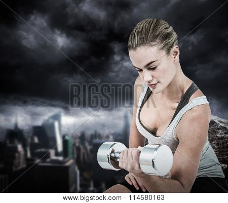 Muscular woman working out with dumbbells against large rock overlooking dark city Muscular woman working out with dumbbells on white background