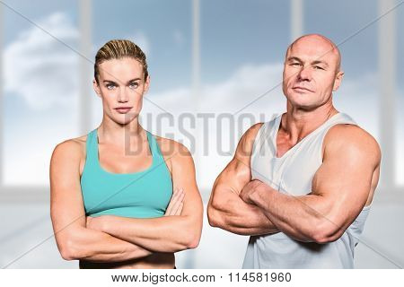 Portrait of athlete man and woman with arms crossed against bright white room with windows