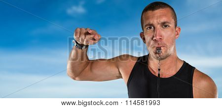 Portrait of attentive trainer blowing his whistle against blue sky