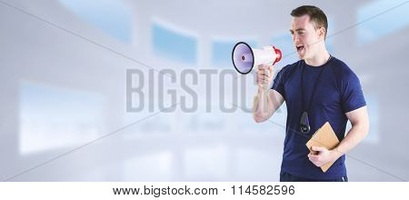 Male trainer yelling through the megaphone against bright white room with windows