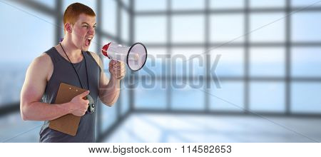 Angry personal trainer yelling through megaphone against room with large window showing city