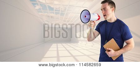 Male trainer yelling through the megaphone against blue sky seen through window