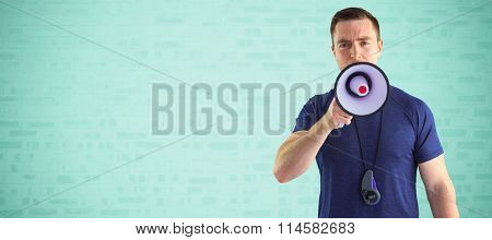 Male trainer yelling through the megaphone against blue brick background