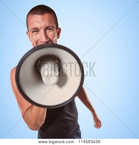Male trainer yelling through megaphone against blue background