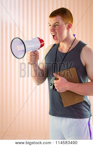 Angry personal trainer yelling through megaphone against peach background